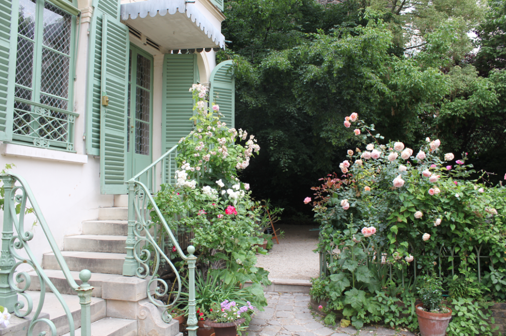 View of a short flight of stairs leading up to an entrance with green shutters. Rose bushes stand next to the house