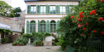Front of a pink house with green shutters. Rose bushes in the right of the frame