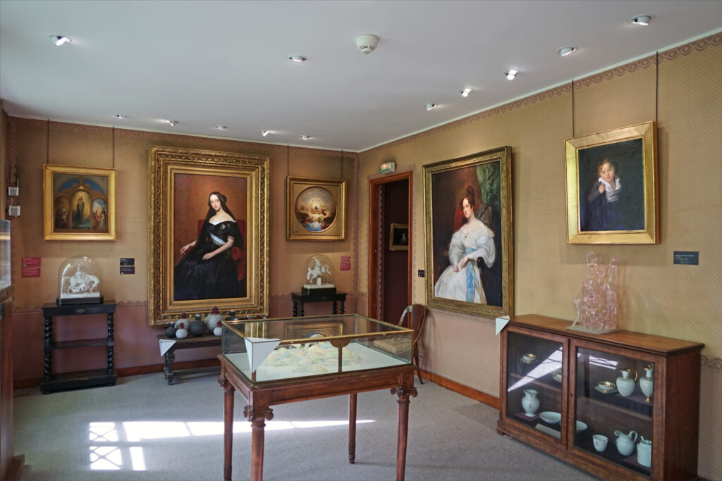 Inside of an exhibition room with grand paintings on the walls